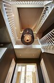 Blick nach oben ins Treppenauge mit Kronleuchter, an Treppenlauf weisses Holz Balustradengeländer