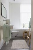 Modern bathroom with designer bathtub below window; stool and ladder-style towel rack made from plain wood