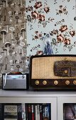 Retro radio on cabinet against wall with two patterns of wallpaper