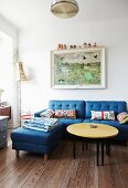 Round coffee table with yellow top, blue sofa with matching ottoman and picture on wall in simple living room