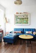 Runder Couchtisch mit gelber Tischplatte und blaues Polstersofa mit passendem Fussschemel in schlichtem Wohnzimmer, an Wand Gemälde