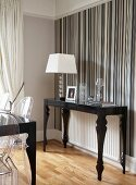 Postmodern, black console table and table lamp with white lampshade against wall with striped wallpaper in various shades of grey