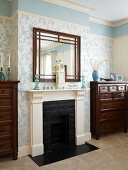 Mirror above fireplace with white surround flanked by chests of drawers in room with floral wallpaper and blue frieze