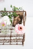 Vintage wire basket decorated with vases of flowers and souvenir photo