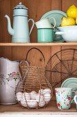 Enamel crocker, wire egg basket & other vintage kitchen equipment in dresser