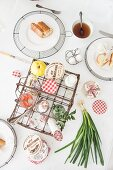 Top view of set breakfast table with various foodstuffs in vintage wire basket