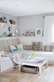 White, rustic coffee table in front of corner bench with seat cushions and scatter cushions in modern living room painted pale grey