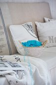 Small basket of crochet supplies with pale blue wool on bench