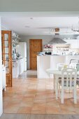 Open-plan kitchen with white dining set