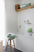 Toiletries and towels on wooden stool next to bathtub with white-tiled surround in corner of bathroom