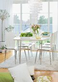 Spring atmosphere in bright dining room - modern chairs around white dining table in front of balcony doors, pile of cushions on floor in foreground