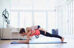 Mother performing yoga exercises with daughter in living room