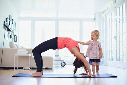 Woman exercising on yoga mat in living room next to inquisitive daughter