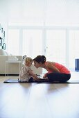 Mother and daughter sitting on yoga mat in living room