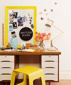 Pin board in yellow-painted antique frame and vintage ornaments on 70s desk next to yellow wooden stool