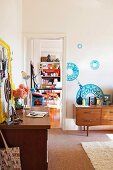 Floral wall stickers above 70s sideboard, yellow-framed pin board above desk and doorway leading into a colourful room