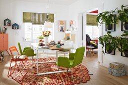 Freundlich möbliertes Esszimmer, grün gepolsterte Stühle und Klappstuhl um weissen Tisch auf Designer Teppich, an Wand Hänge-Blumentöpfe