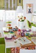 Mit Desserts gedeckter Tisch, farbige Tassen auf farbigen Tischsets, im Hintergrund halb heruntergelassene Rollos an Balkontür