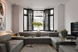 Grey, modern sofa combination in front of bay window and Christmas arrangement suspended from ceiling