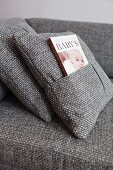 Grey marl cushion cover with book inserted in integrated pocket