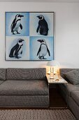 Retro table lamp on narrow side table between grey marl sofas below picures of penguins on walls