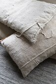 Vintage-style cushions with ecru linen covers on grey woven carpet