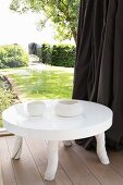 Low, white table with glossy top and rustic legs next to glass wall with view into summery garden