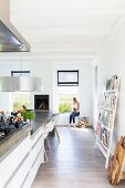 Designer kitchen counter continuing into dining table; young woman and cat sitting next to window in background