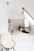 Modern teenager's bedroom with sloping ceiling and white sheepskin blanket on wicker chair