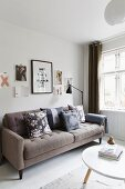 Beige, retro sofa with scatter cushions in various patterns below pictures on wall