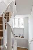 Stairwell with white-painted wooden staircase in period apartment