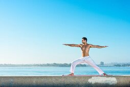 A young man by the sea wearing white yoga trousers