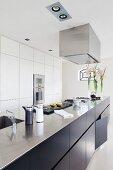 Long, free-standing kitchen counter with dark base units in designer kitchen