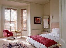 Doppelbett mit roter Auflage und Sitzplatz in Fenstererker; Streiflicht durch geschlossene Jalousien