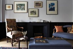 Seating area with antique furnishings, blue ottoman and fireplace integrated into dark wainscoting