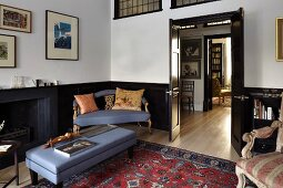 Antique sofa and ottoman with matching blue covers combined with Oriental rug and traditional Rococo armchair
