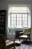 30s armchairs on Oriental rug and delicate side table below lattice window in living room