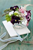 Spring posy of pansies, violas, astilbes, lilac, flowering currant and apple blossom with ribbon on white tile