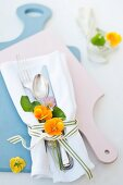 Cutlery on white linen napkin decorated with yellow and purple violas