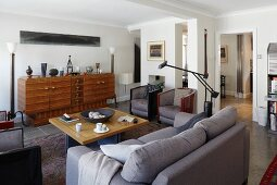 Modern sofa, Art Deco, teak sideboard and retro armchair around square table in classic, elegant interior