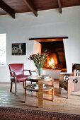 Chair, armchair and round table in front of open fire in rustic, eclectic interior