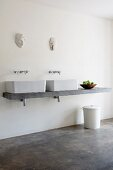 Concrete washstand with twin countertop basins below wooden masks on wall