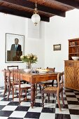 Dining area with antique chairs and table on chequered floor in rustic interior