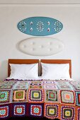Bed with white pillows, patchwork blanket, and decorated panels above wooden headboard