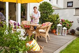 Summery seating area with wicker furniture on DIY wooden terrace