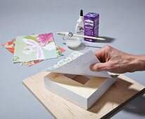 Instructions for making a DIY wooden frame covered in wallpaper remnants or wrapping paper