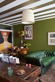 Green Chesterfield sofa, green accent wall and green and white striped ceiling in open-plan living are