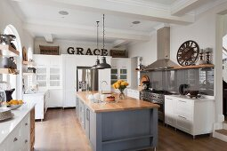 White, country-house kitchen with free-standing, grey counter and glass splashback behind cooker in traditional interior