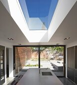 Point 7, Winchester, United Kingdom. Architect: Dan Brill Architects, 2014. View from kitchen to sunny terrace on multiple levels through sliding terrace doors