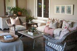 Rattan Sessel und Sofa mit Kissen um Couchtisch auf wohnlich eingerichteter, geschützter beigefarbener Veranda